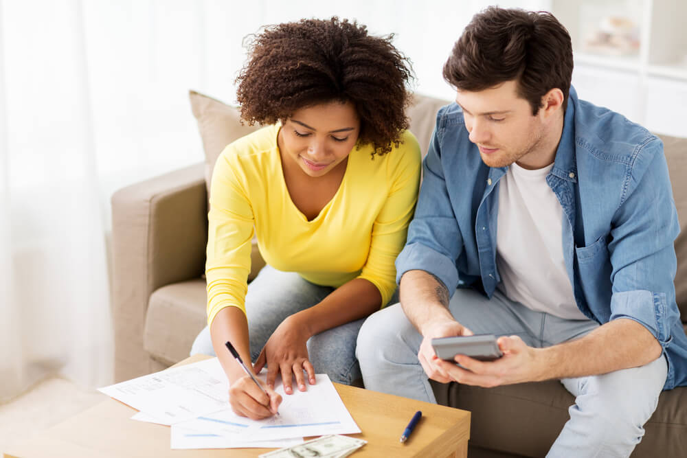 man and woman filing taxes together on living room