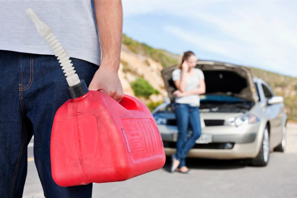 young man is holding a gas can while a woman talks on a cell phone by the car roadside assistance