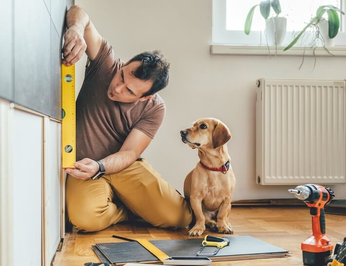 man doing home reperations with a dog diy home projects