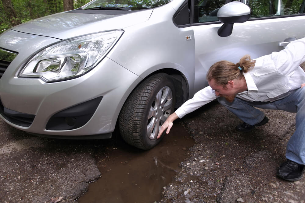upset man looking at pothole damage to his car how to avoid potholes