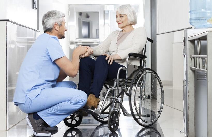 doctor taking care of elderly woman on wheelchair long term care coronavirus