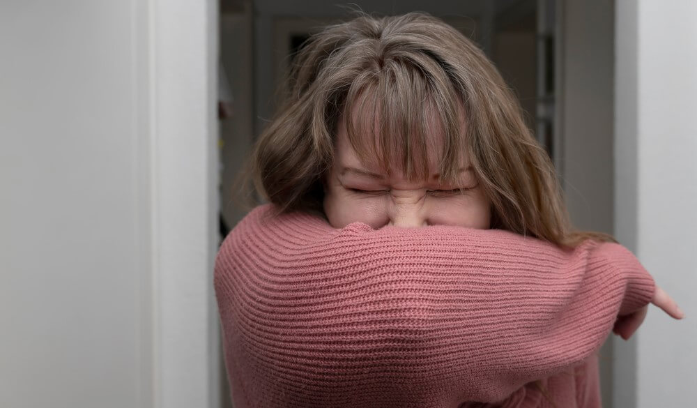 woman practices sneezing etiquette to protect yourself against coronavirus