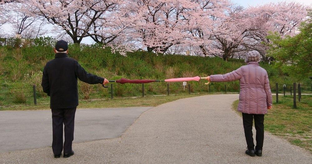 couple social distancing in park with umbrella prevent coronavirus