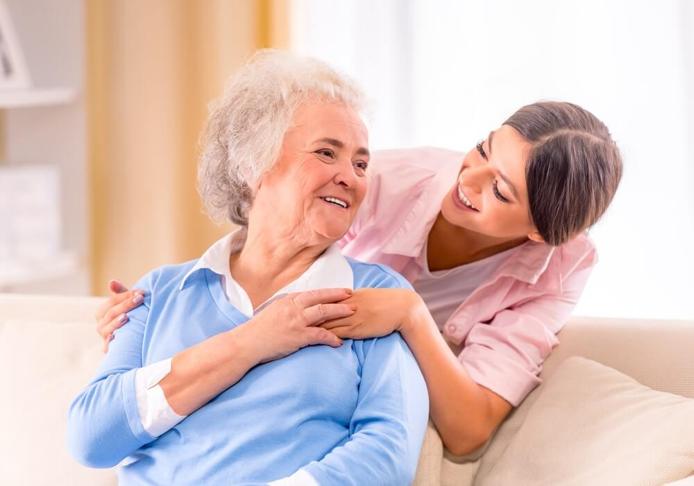 nurse talking to senior woman at in home care