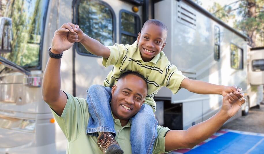 african american father and son enjoying a used travel trailer