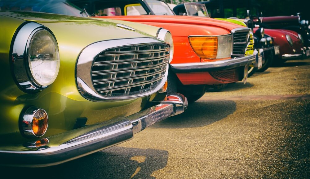 row of classic and antique cars parked