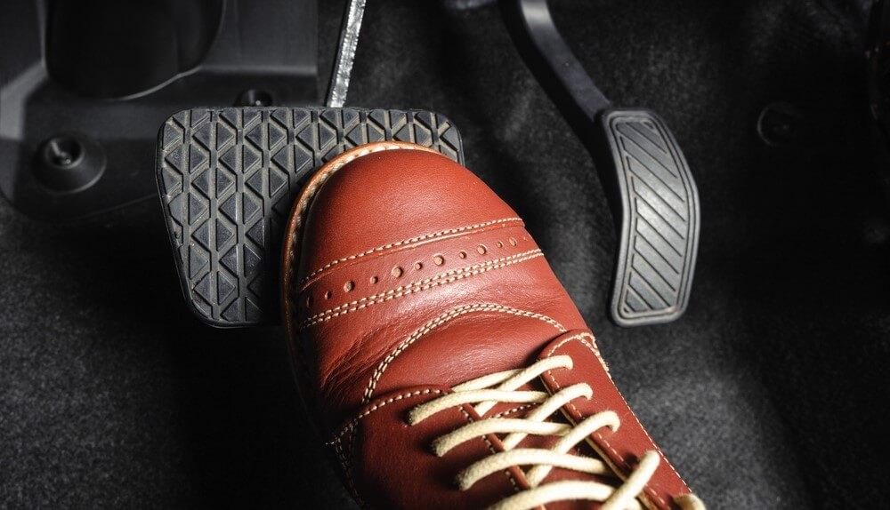 foot hitting the anti-lock breaks on a car