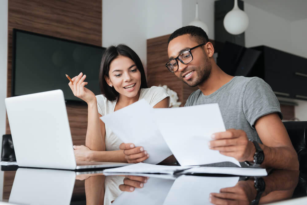 young couple checking their business finances on laptop with bond insurance