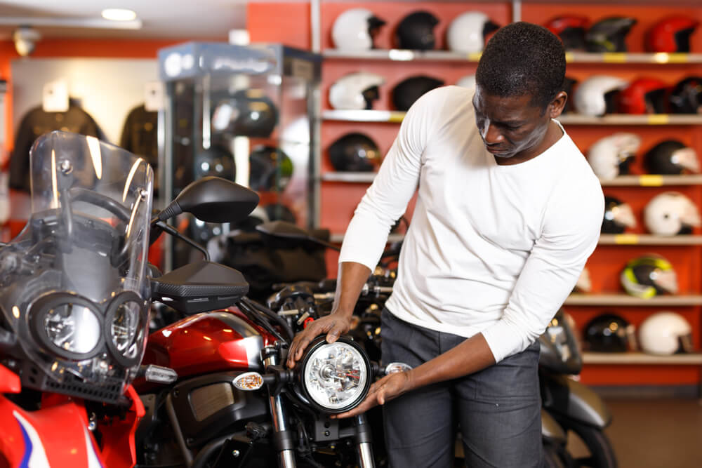 african american man inspecting a used motorcycle on a shop