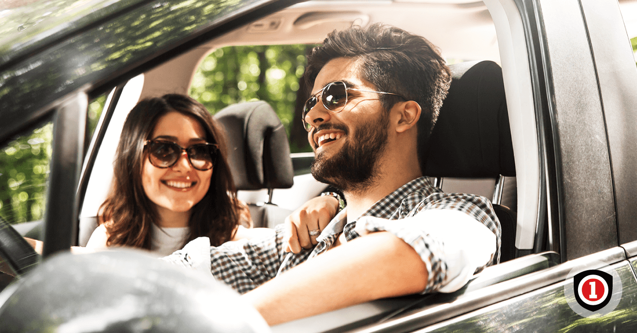 Hispanic couple Driving and smiling while they're covered by Auto Insurance