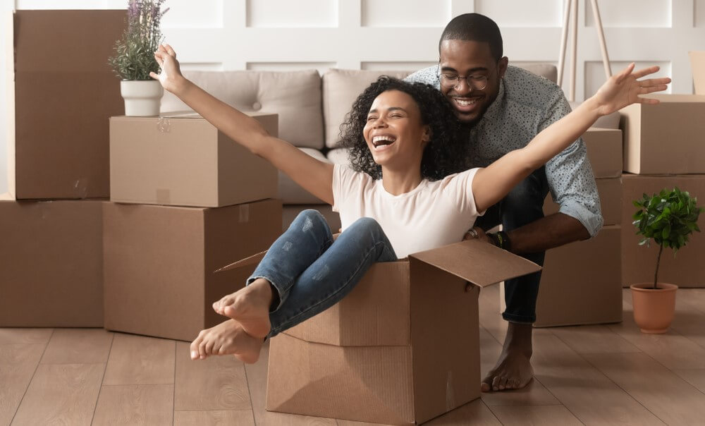 happy couple playing with moving boxes while renting for the first time