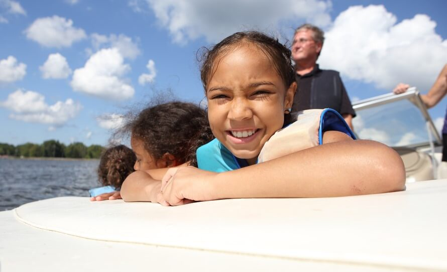 happy little girl on boat with watercraft insurance
