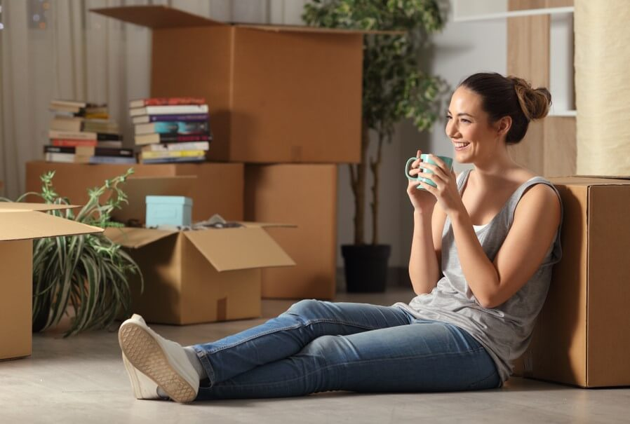 happy woman sitting in her rented apartment