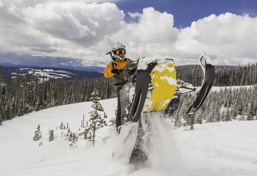 man on snowmobile jumping on a snowy mountain