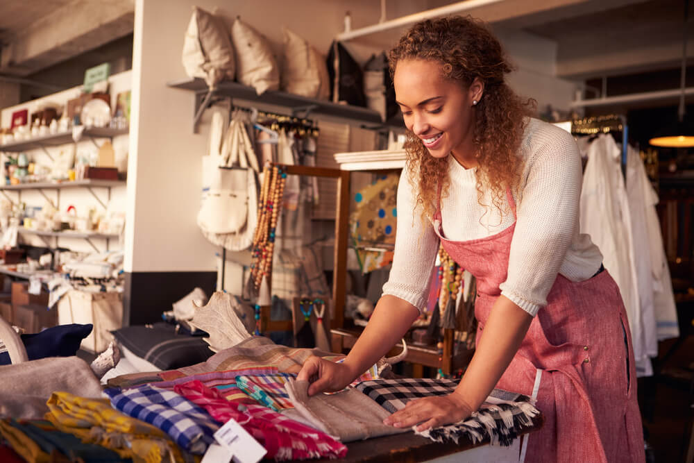 african american woman smiling and folding clothes in her  small business with insurance