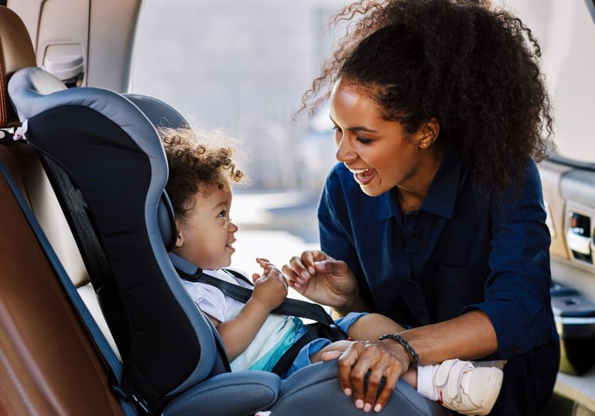 happy african american mother strapping traveling with children in car seat