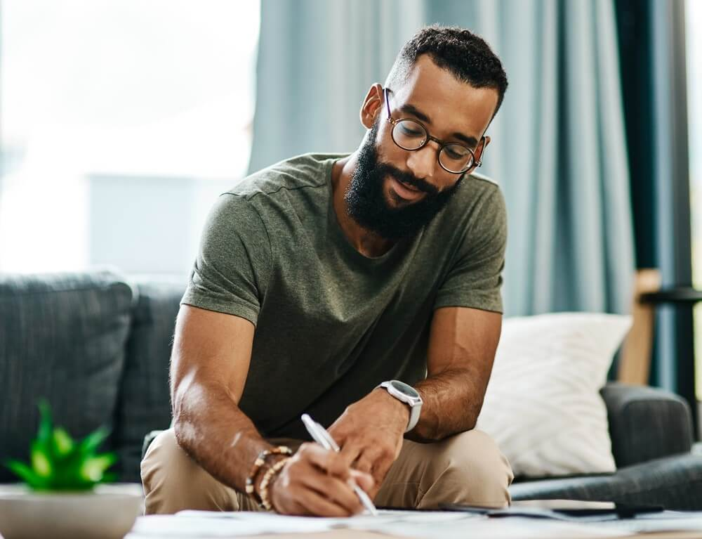 african american man writing on paper while buying homeowners insurance