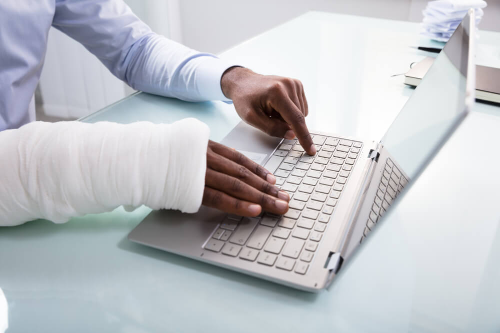 Close-up Of A Businessman With Bandage Hand Using Laptop At Workplace asking how does disability insurance work