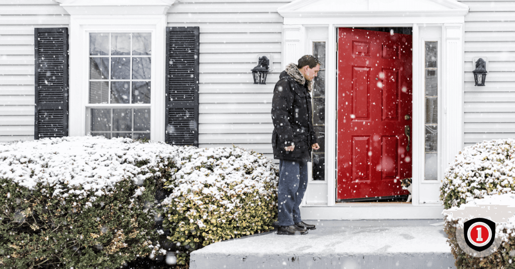 A man outside his home while winter weather