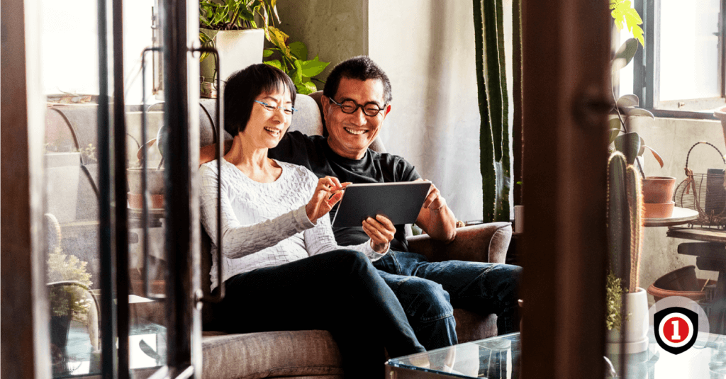 Asian couple smiling in their living room while they covered by home insurance
