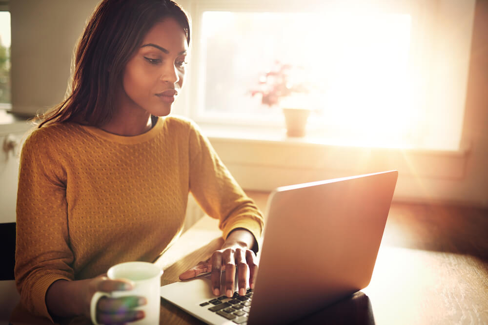 young african american woman looking at the types of homeowners insurance in laptop