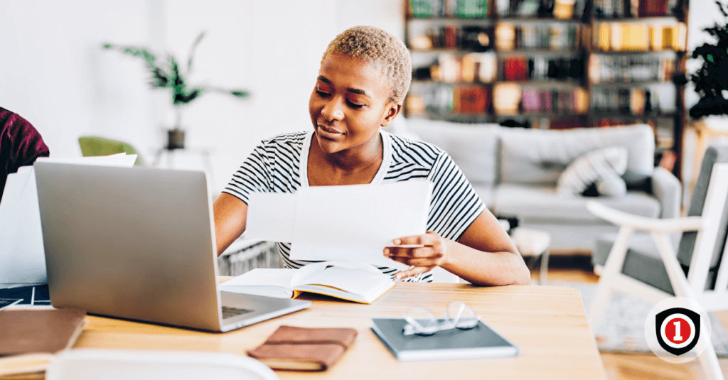 An african america women calculating how much renters insurance coverage needs while she use her computer
