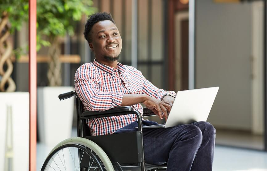 smiling african american man sitting in wheelchair and using laptop
