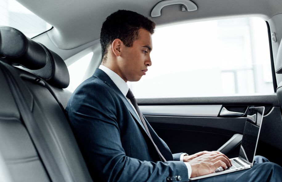 side view of african american businessman using laptop in car with insurance