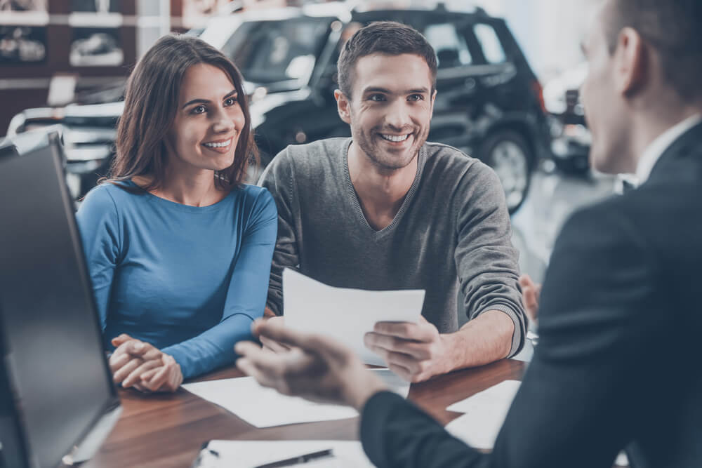 happy couple buying a new car with insurance