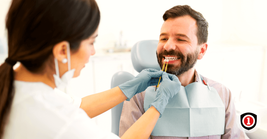 A man smiling while he's with his dentist