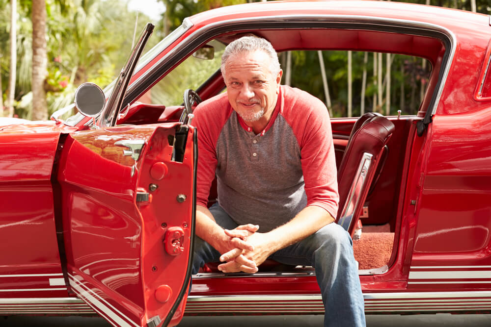 male senior man sitting in his classic car