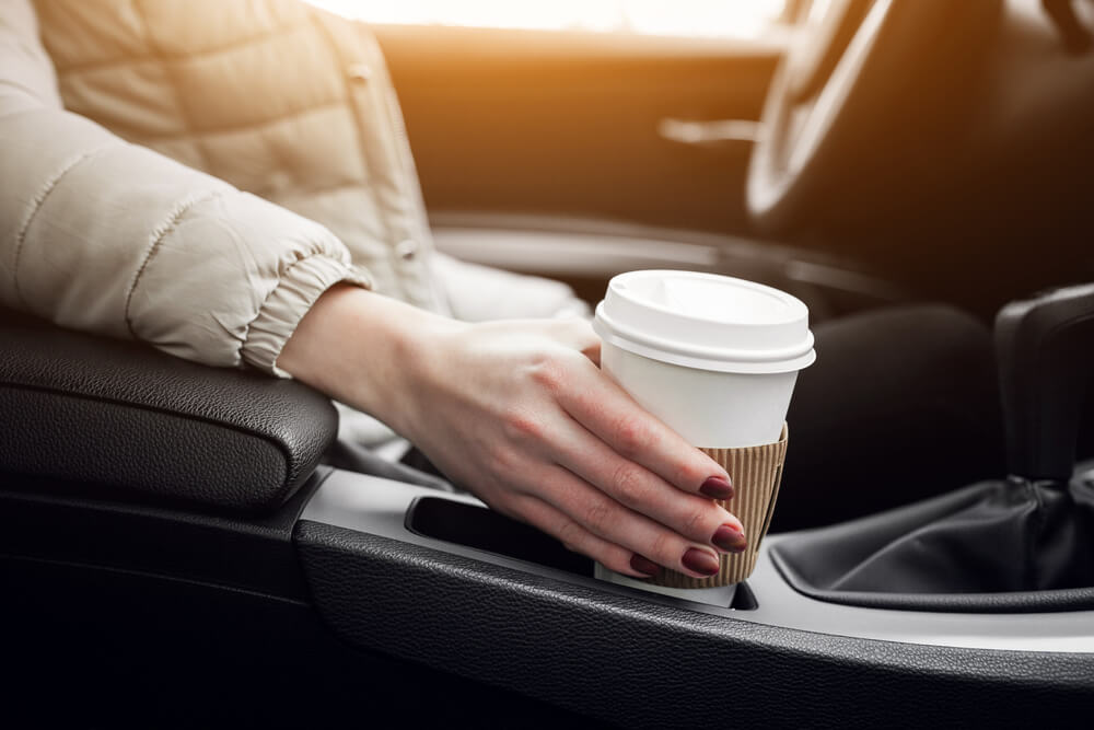 woman holding coffee cup on car holder