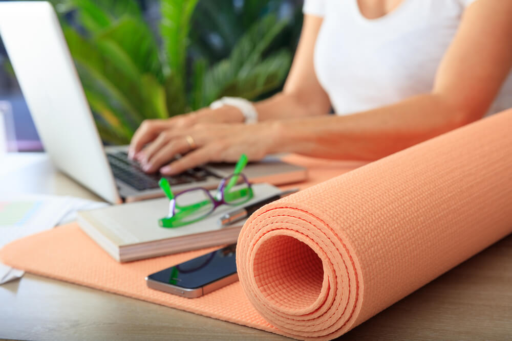 Yoga mat in an office desk with woman working in the background