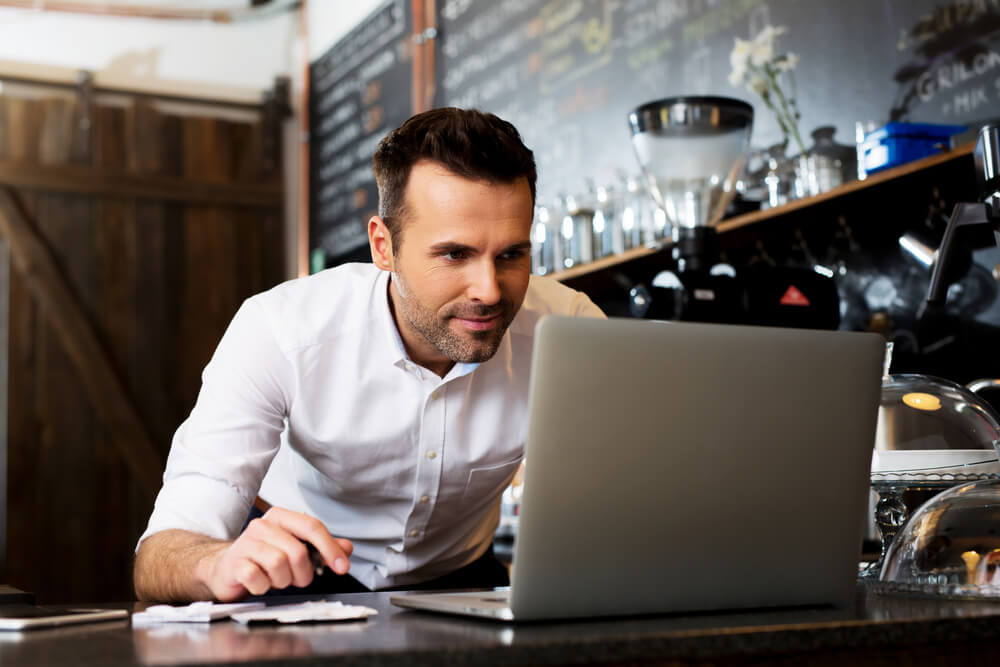 business owner in shop with laptop looking for insurance