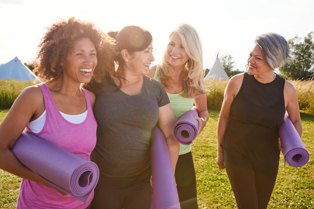 group of mature women in park taking yoga with whole life insurance