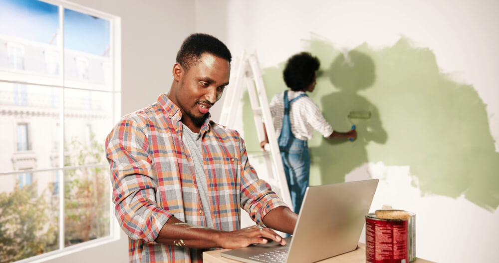 happy man with laptop with his wife painting the wall in the background